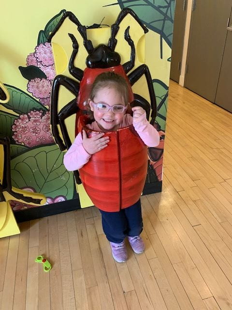 child wearing bug costume at children's museum