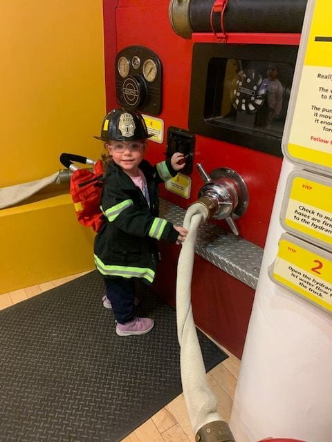 child wearing firefighter costume at the children's museum