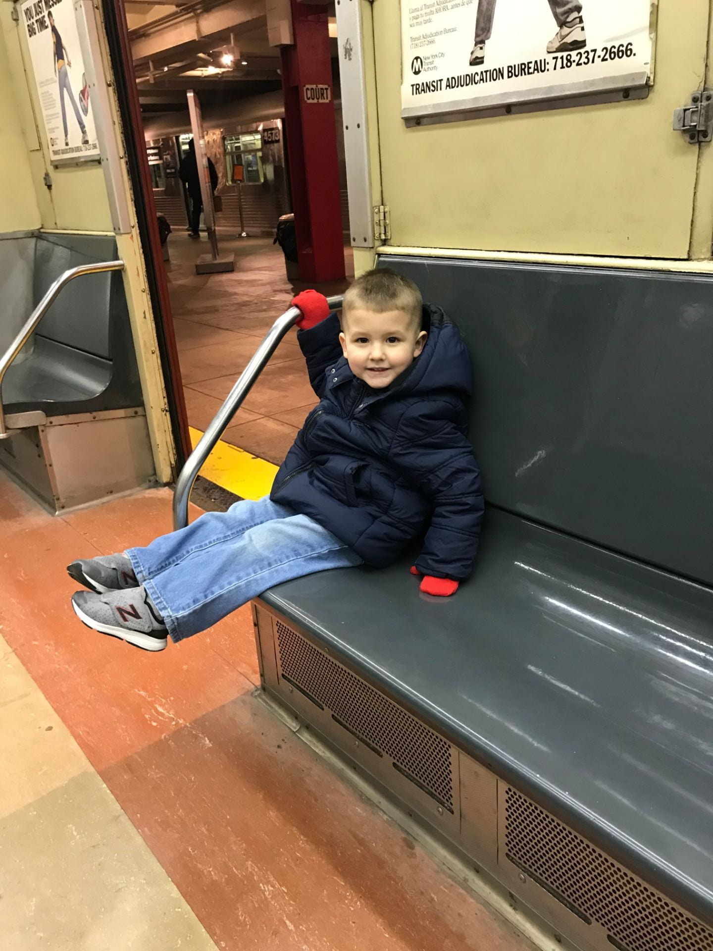 child sitting on a bus at the new york city transit museum