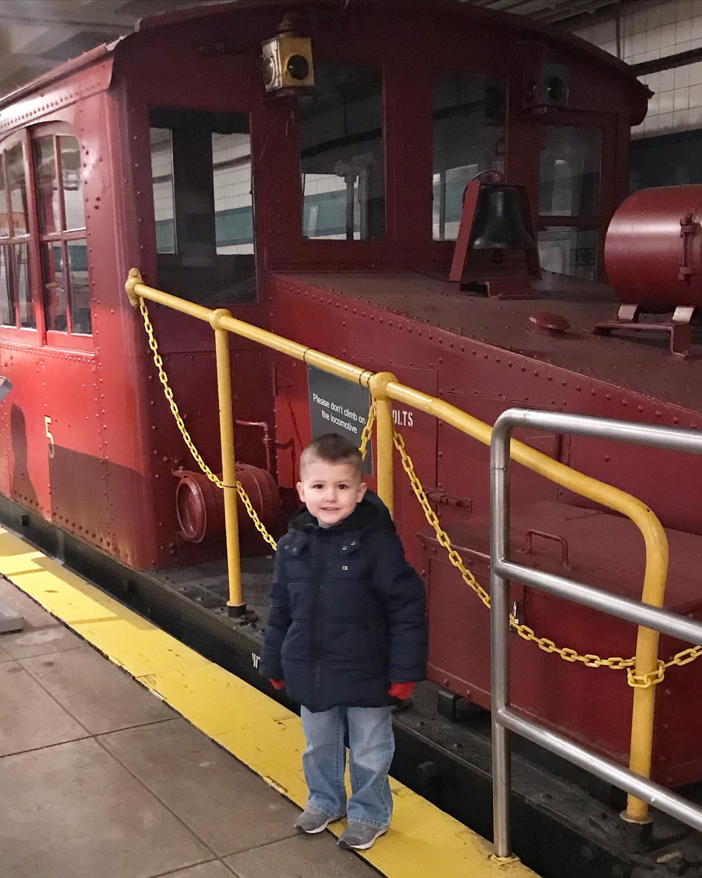 child standing by an old train at the NYC transit museum