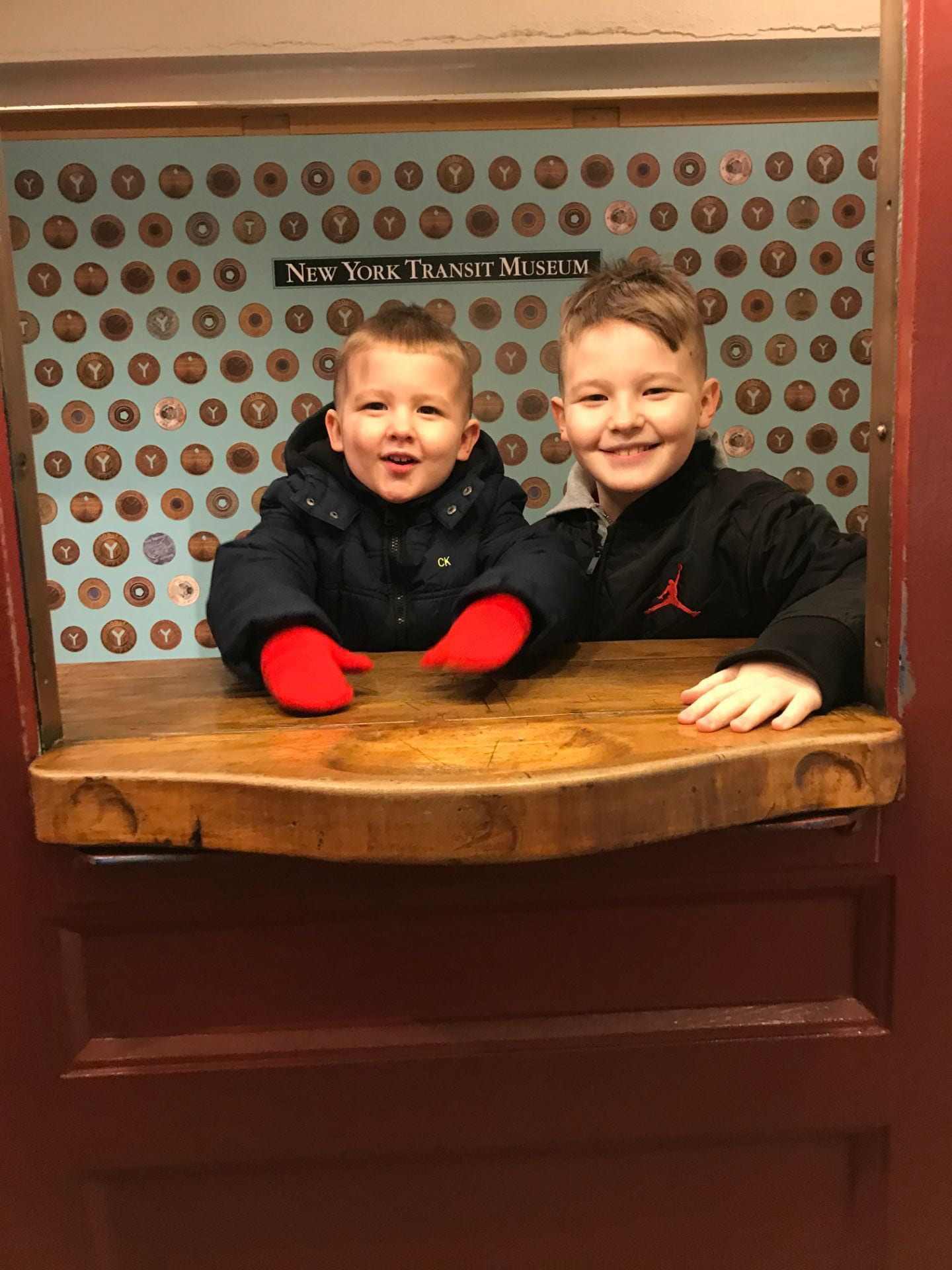 children standing in the ticket booth at the NYC transit museum
