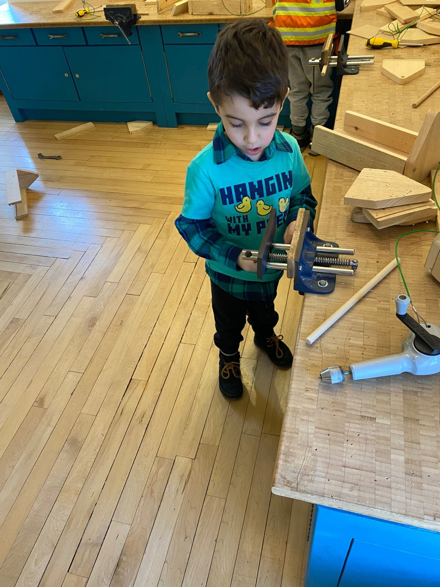 child building with tools and wood at snug harbor children's museum