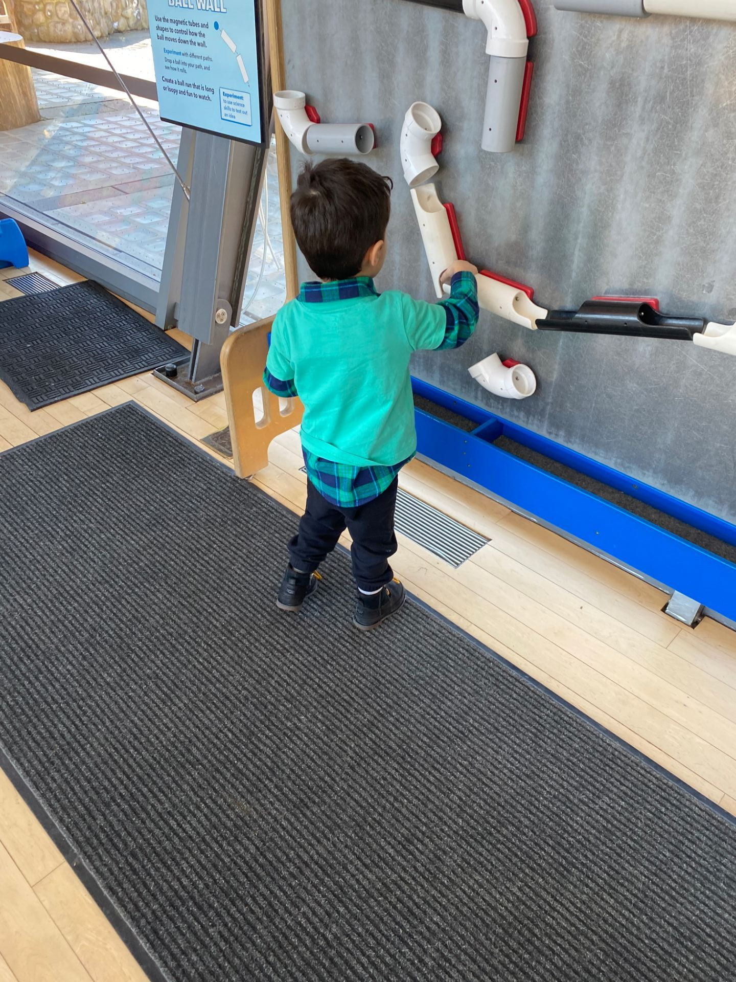 child exploring the ball wall at snug harbor children's museum
